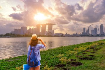 Young woman traveler with sky blue backpack and hat holding the map with singapore city downtown background
