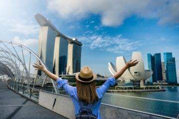 Young woman traveler with backpack and hat traveling into singapore city downtown