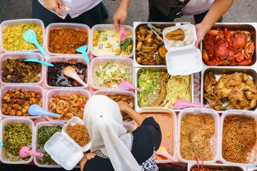 Overhead shot of people buying food over variety of delicious Malaysian home cooked dishes